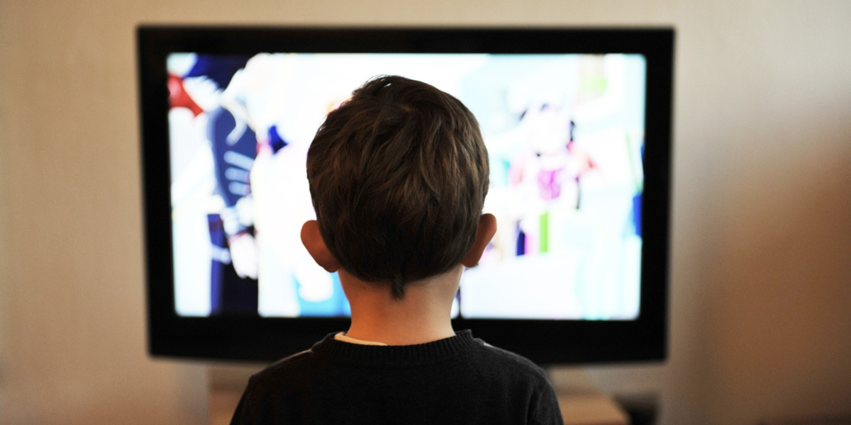 Young boy watches a TV screen